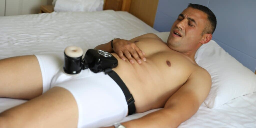 A man shows an expression of pleasure while lying down while wearing a Male Humpus over white briefs.